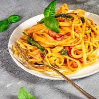 Cremig, vegane Pasta mit Tomaten Alfredo Soße und sonnen-getrockneten Tomaten und Spinat