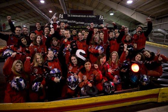 Pequeño grupo de compañeros de trabajo que van a competir en karting en uniformes rojos