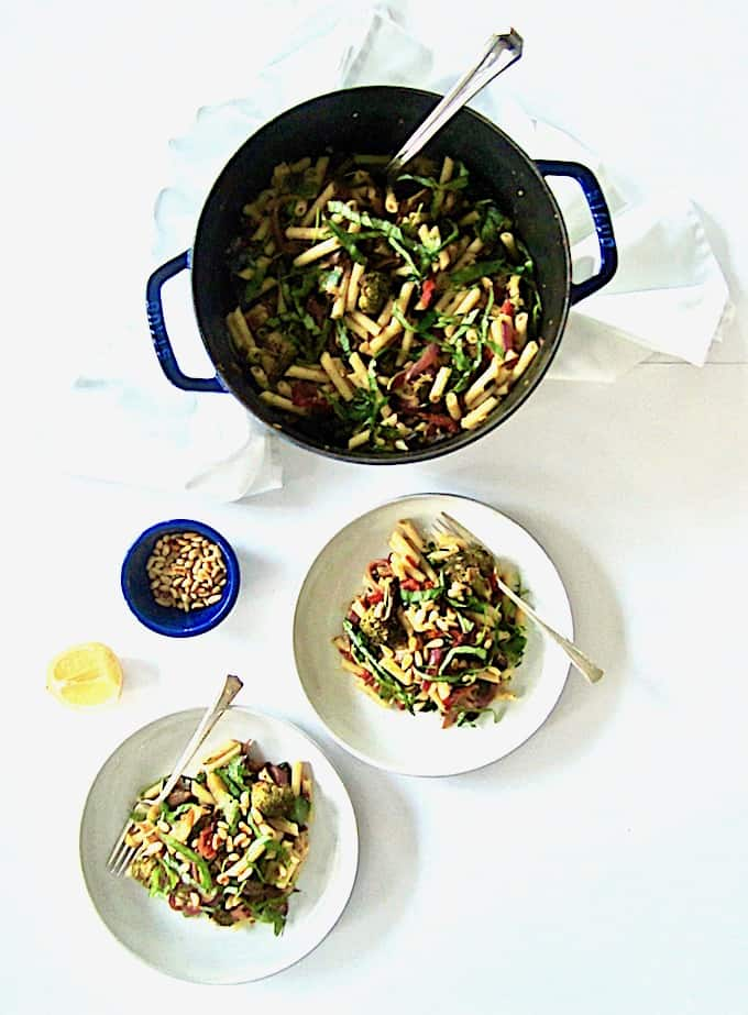 An easy, healthy, vegan and gluten free Italian penne pasta recipe featuring a garlic and balsamic roasted vegetable medley of broccoli, mushrooms, red onion, zucchini and chopped almonds for crunch. Toss it all together with sun-dried tomatoes, arugula, basil and pine nuts and you have a vibrant and colorful dish bursting with fresh flavor.