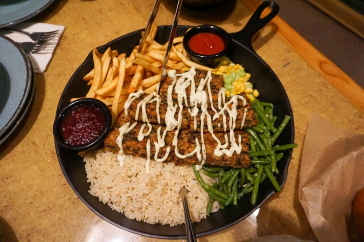vegan loaf with vegan cream sauce, rice, green beans, corn, and fries in skillet