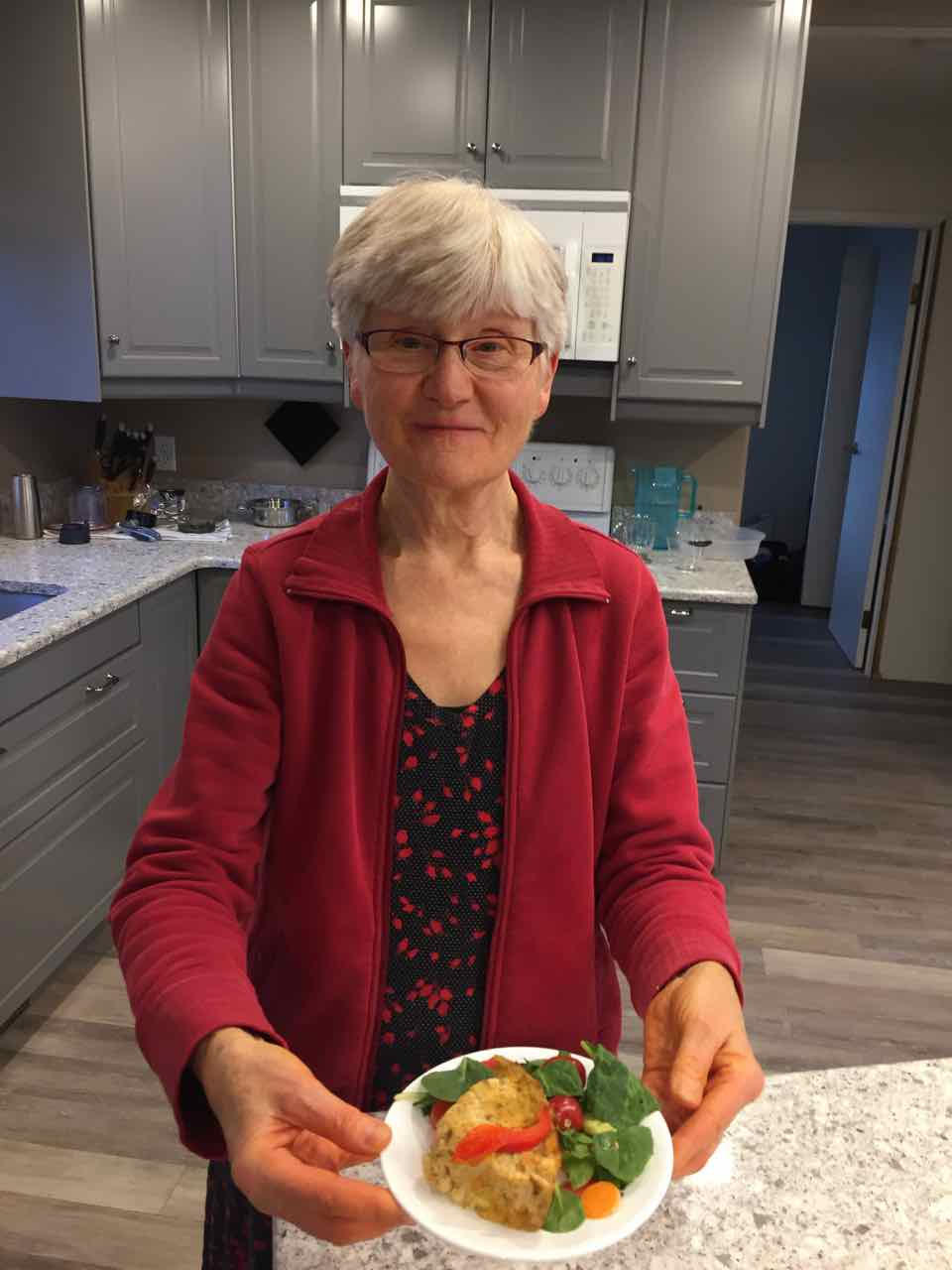 Image of Daisy Perry (my mom) presenting a piece of her gluten free easy vegan tofu quiche.