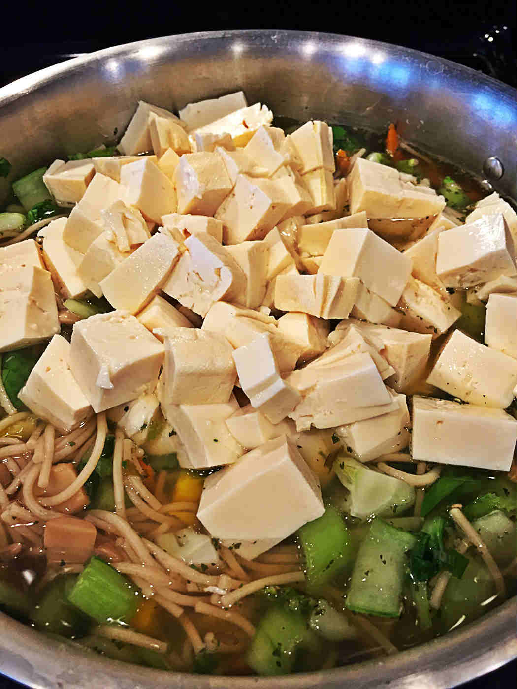 Adding the tofu to the soup