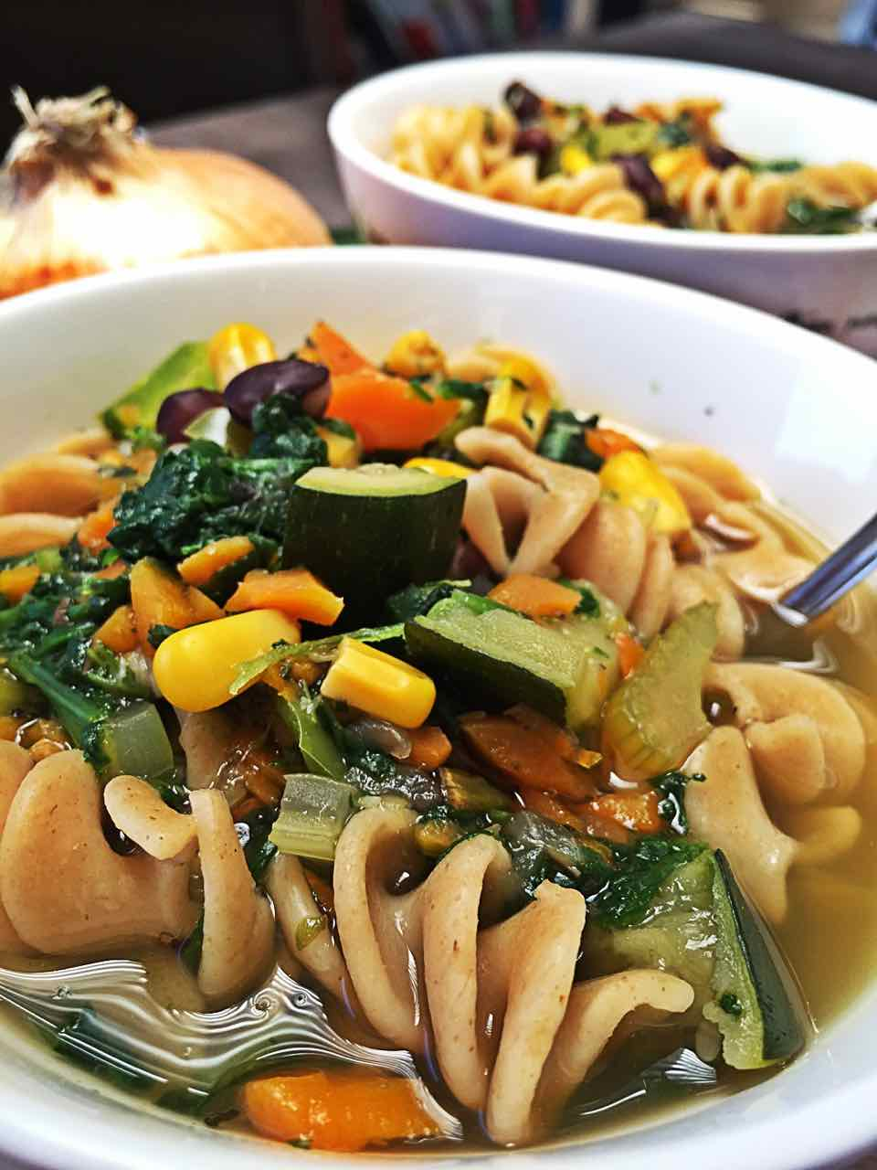 Image of close up vegan green vegetable medley soup in bowl, with pasta and carrots and spinach and black beans and zucchini, it looks very delicious.