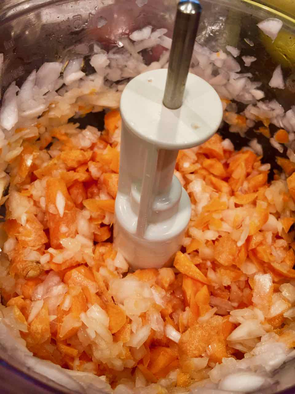 Image of chopped onion and carrots in a food processor.