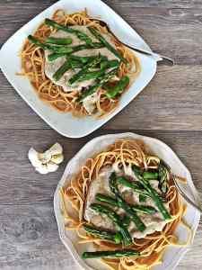 Image of two plates of vegan creamy pesto linguine with asparagus