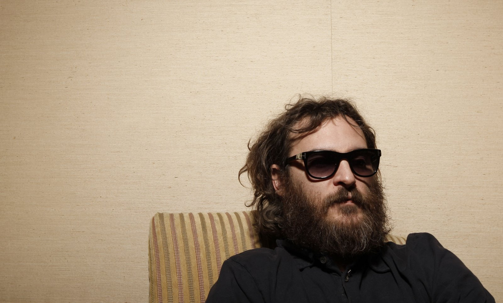 Actor Joaquin Phoenix poses for a portrait in Beverly Hills. He has a huge beard and is looking very scruffy.