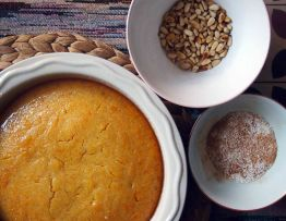 soak the baked cake in syrup, sprinkle with desiccated coconut and cinnamon powder and then toasted pine nuts