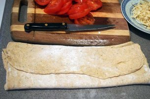 fold rolled dough ready to transfer to hot baking tray