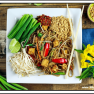 overhead view of vegan pad thai on a white plate. Chop sticks and blue napkin on the side