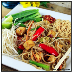 side view of vegan pad thai on a white plate with chopsticks on the side.