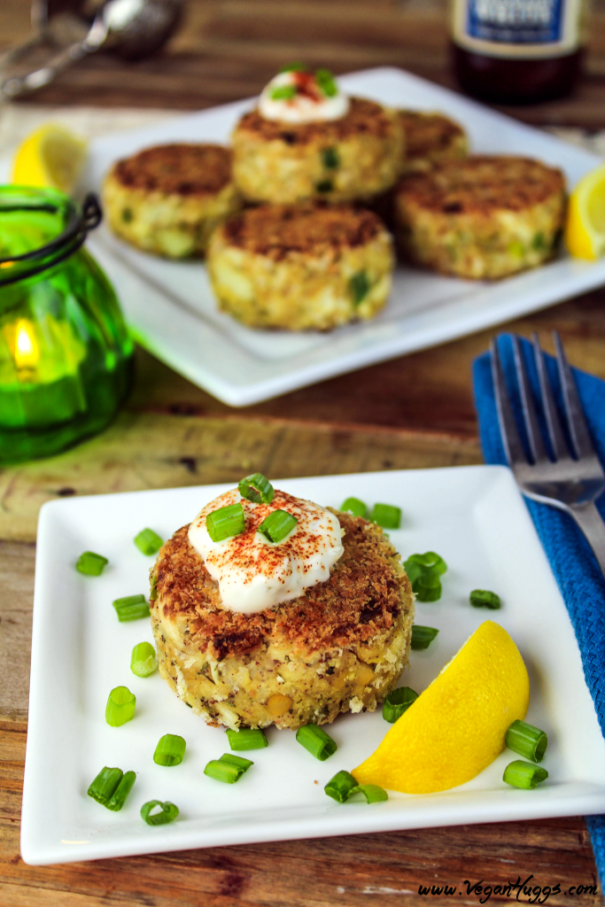 Vegan crab cakes on two serving plates. Green candle in the background with beverage.