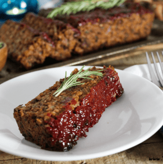 One slice of meatless loaf on a white plate. Full loaf in the background on s ilver serving tray.