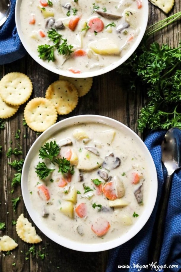 Overhead view of two white bowls of vegan clam chowder. Crackers and spoons on the side.