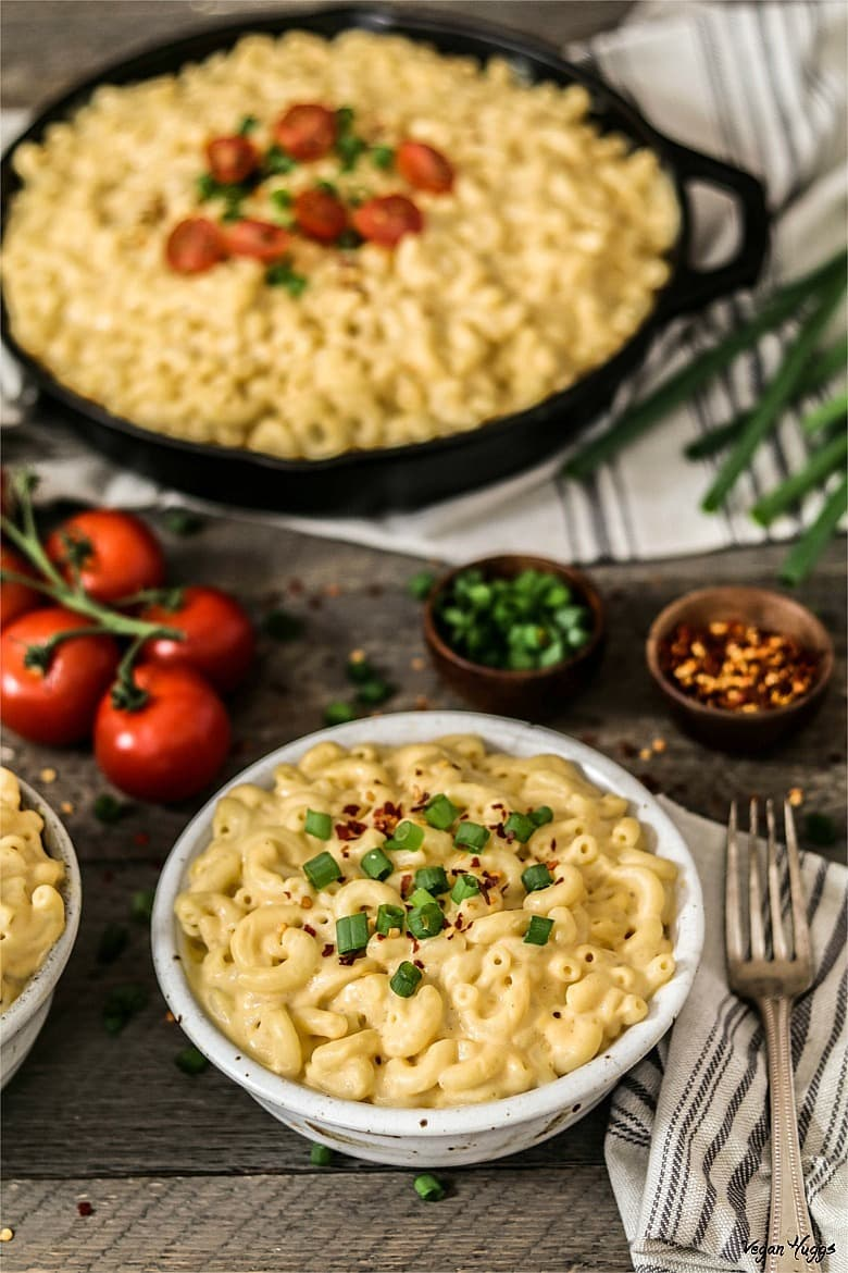 Vertical photo of cooked macaroni in white bowl. Filled cast iron skillet in background.