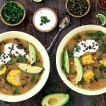 two yellow bowls filled with ajiaco soup. Topped with cilantro, avocado and capers.