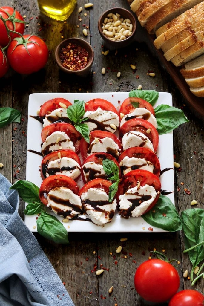 sliced vegan mozzarella cheese on top of sliced tomatoes and on a white square plate.