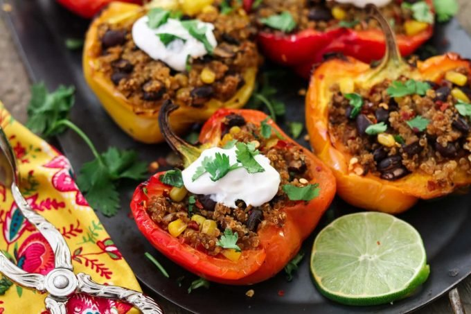 Closeup photo of 4 quinoa stuffed peppers. Topped with sour cream and cilantro.