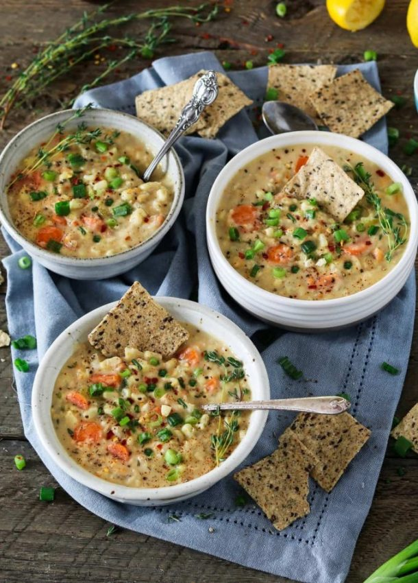 3 bowls of Vegan Corn Chowder with spoons in the chowder. Topped with thyme and crackers.