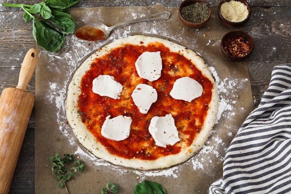Process photo of placing vegan mozzarella cheese on top of sauce.