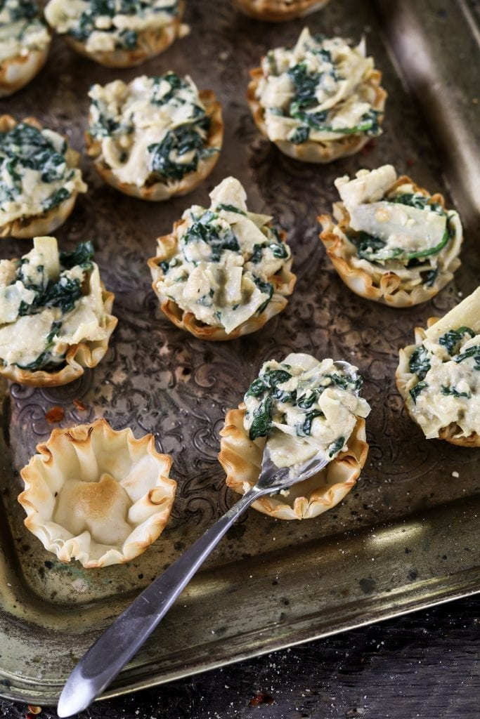Filling process for Vegan Spinach Artichoke Cups.