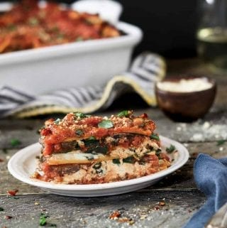 side view of lasagna on a white plate. Casserole in the background.