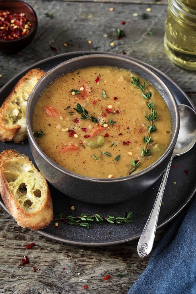 Bowl of Yellow Split Pea soup on a plate with crusty bread on the side.