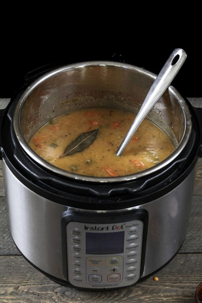 Fully cooked Yellow Split Pea Soup in the Instant Pot with a ladle inside.