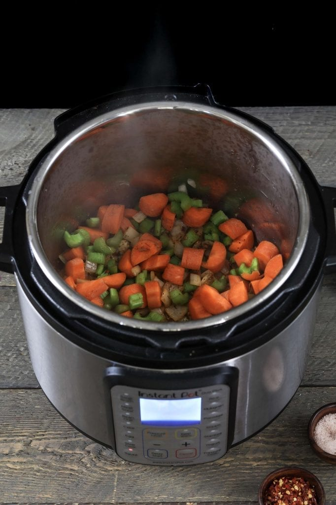 cooking onions, seasonings, celery and carrots in the instant pot.