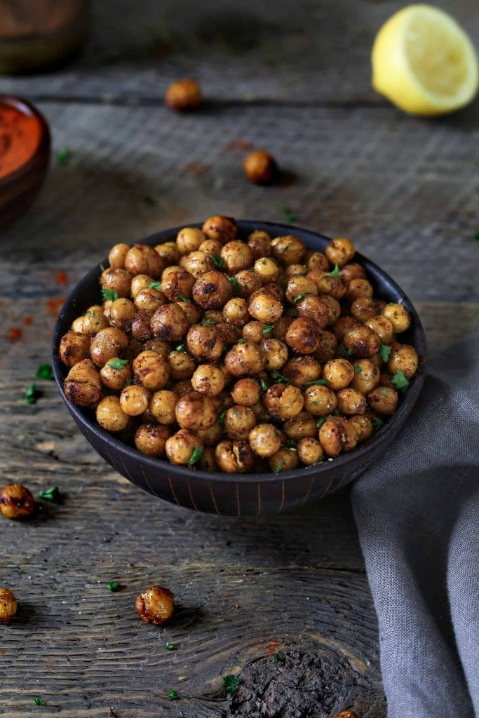 Vertical photo of air fried chickpeas in a black bowl. Topped with fresh parsley.