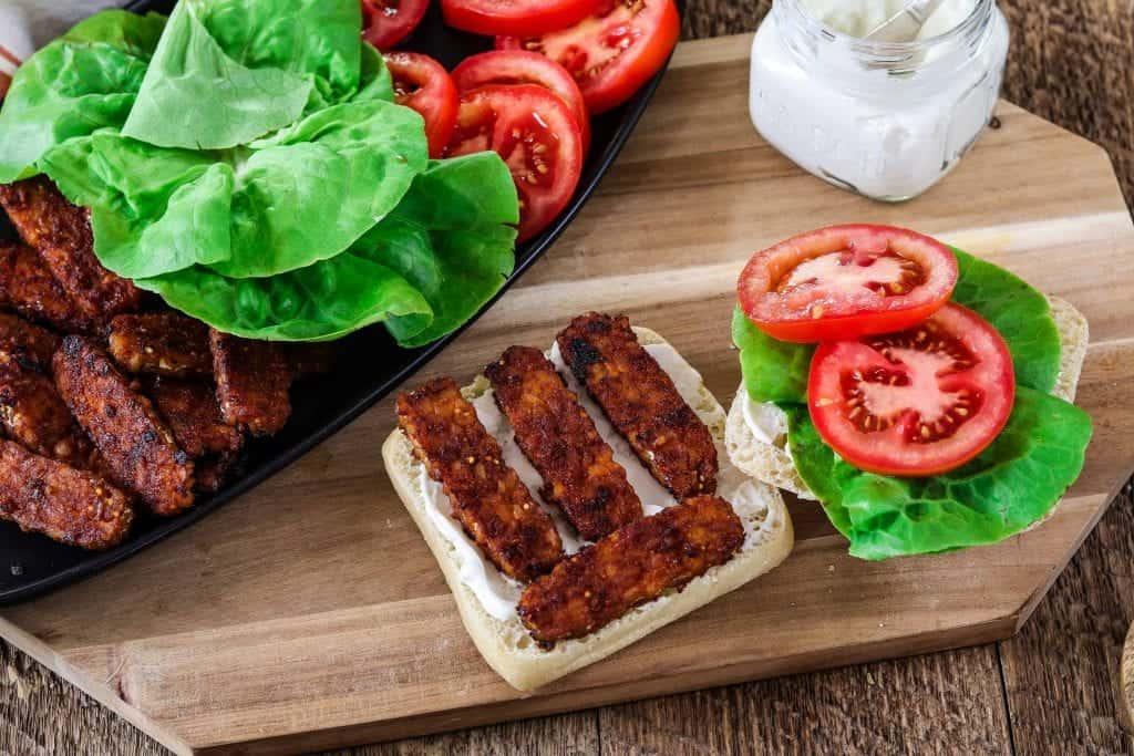Assembling vegan blt sandwich. Mayo in a jar on the side.