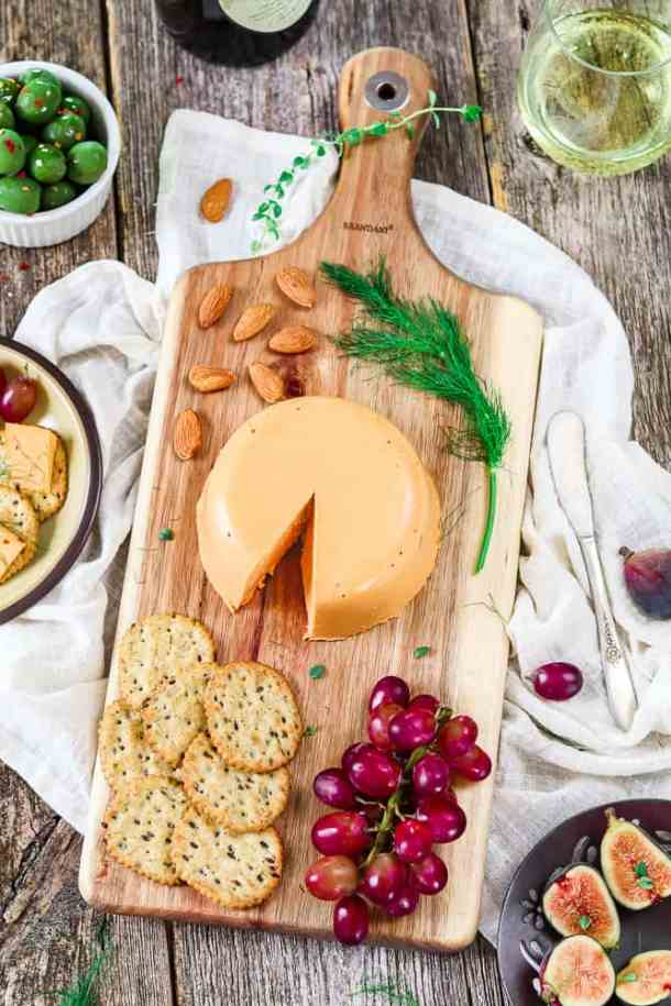 Overhead view of vegan cheddar cheese wheel on a cutting board. Dill, grapes, almonds and crackers on the side.