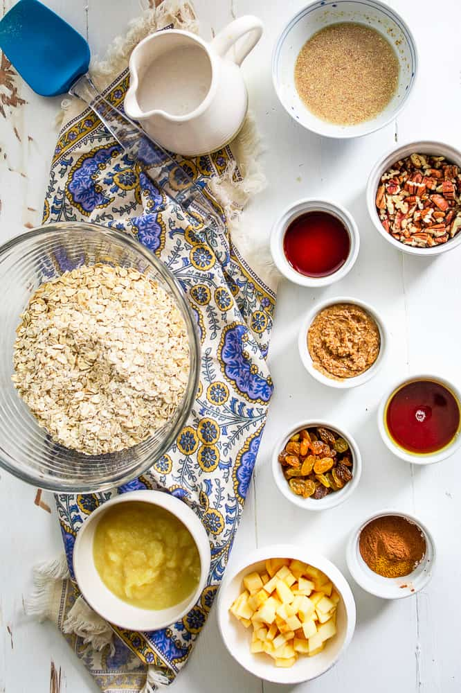 Ingredients for baked oatmeal muffins spread out of a white table in individual bowls.