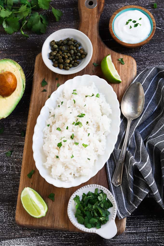 Topping for vegan ajiaco on a wood cutting board. Avocado, rice, capers, vegan sour cream with serving spoon on the side.