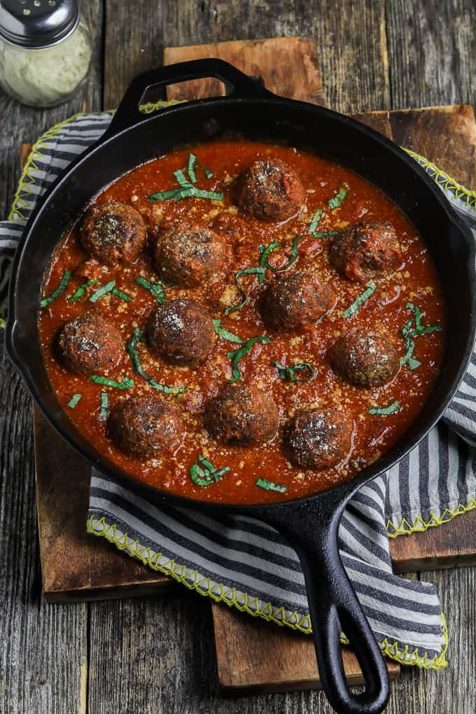 cast iron skillet filled with vegan meatballs and sauce. Garnished with basil.