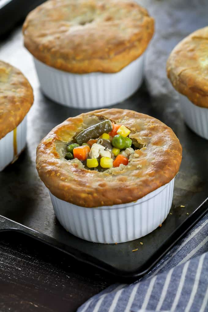 4 fully baked vegan pot pies on a baking sheet with a striped napkin on the side. One vegan pot pie is cut open on top with vegetables showing.