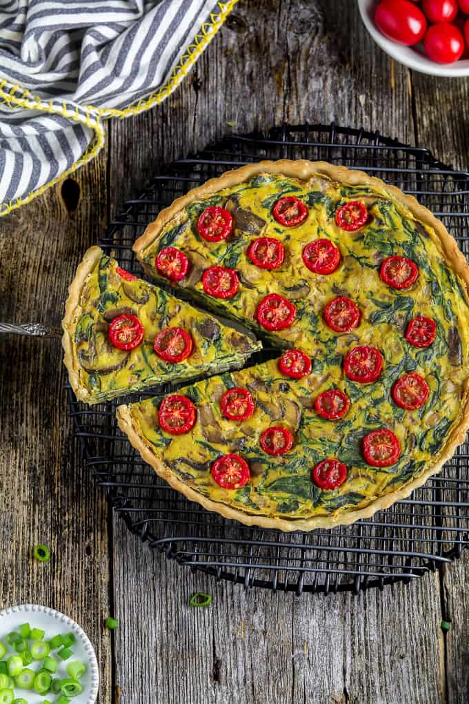 overhead view of easy vegan quiche on a cooling rack with one slice cut out.