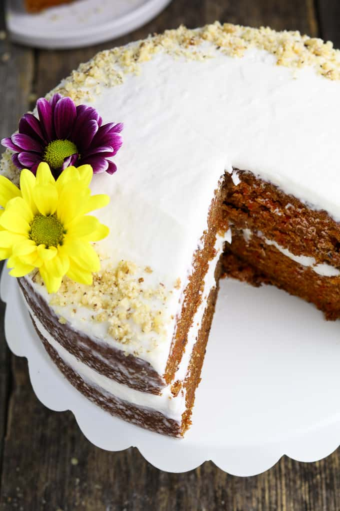 overhead view of vegan carrot cake on a white serving stand and topped with crushed walnuts.