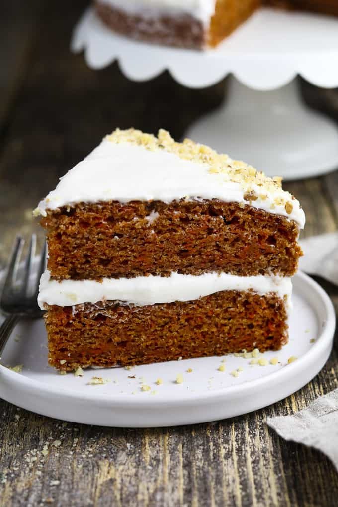 side view of a slice of vegan carrot cake on a white plate with fork on the side.