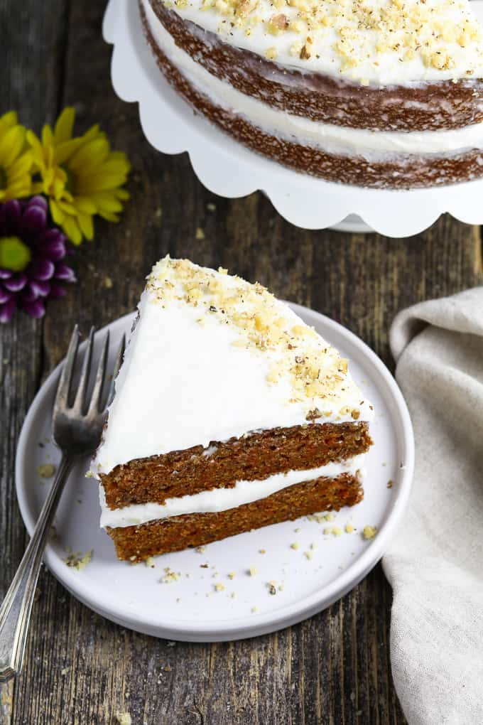 overhead view of a slice of vegan carrot cake on a white plate. Full cake in the background.