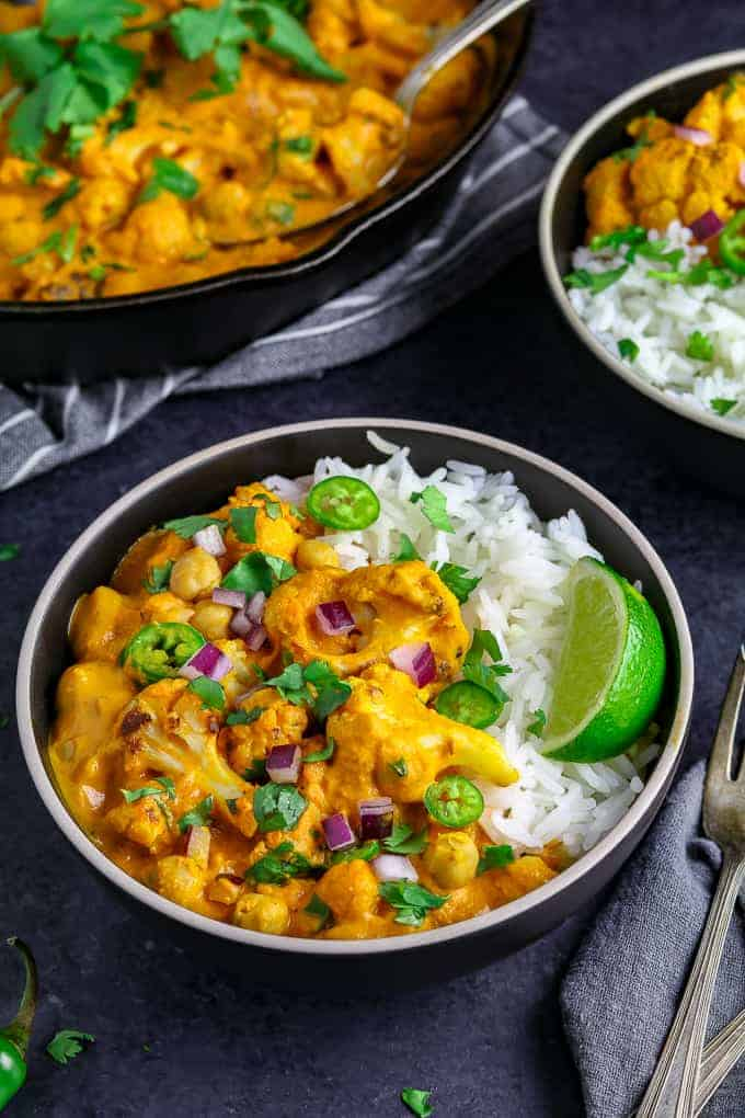 two black bowls filled with chickpea coconut curry and topped with red onion and lime.