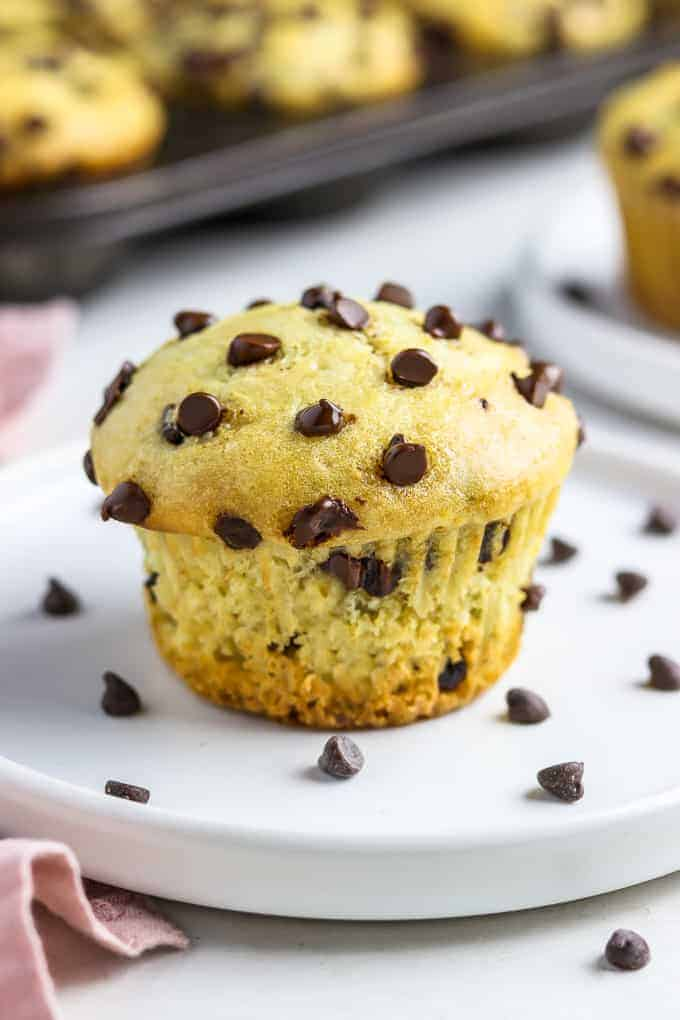 close up photo of vegan chocolate chip muffin on a white plate with more muffins in the background.