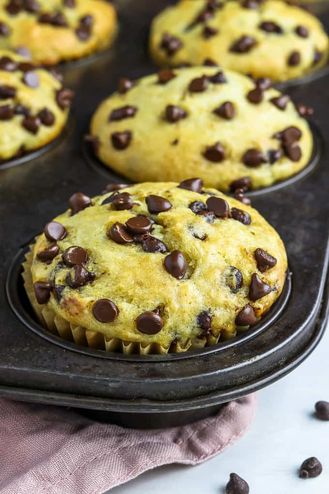Muffin tin filled with fully baked vegan chocolate chip muffins.