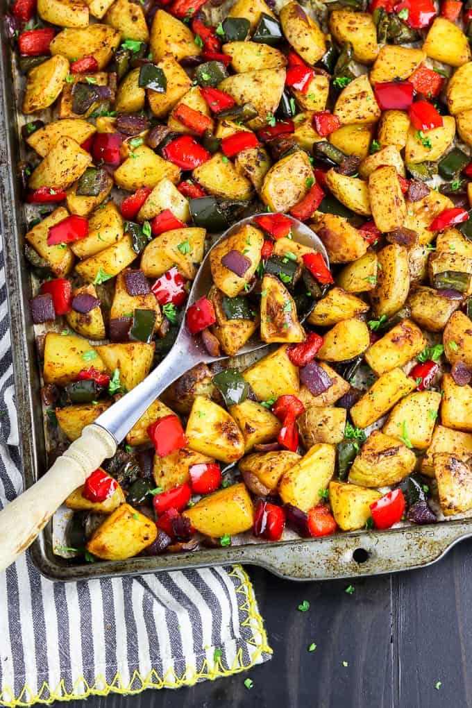 Baking sheet filled with fully roasted breakfast potatoes. Spoon in the middle.