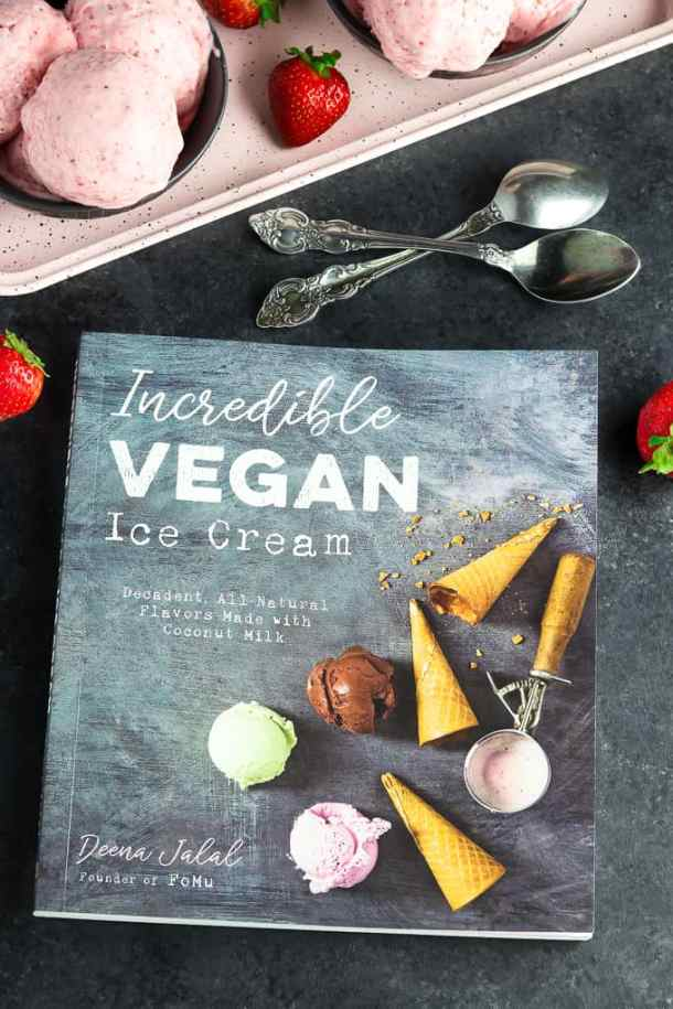 Photo of the Incredible Vegan Ice Cream Cook Book with spoons and ice cream on the table.