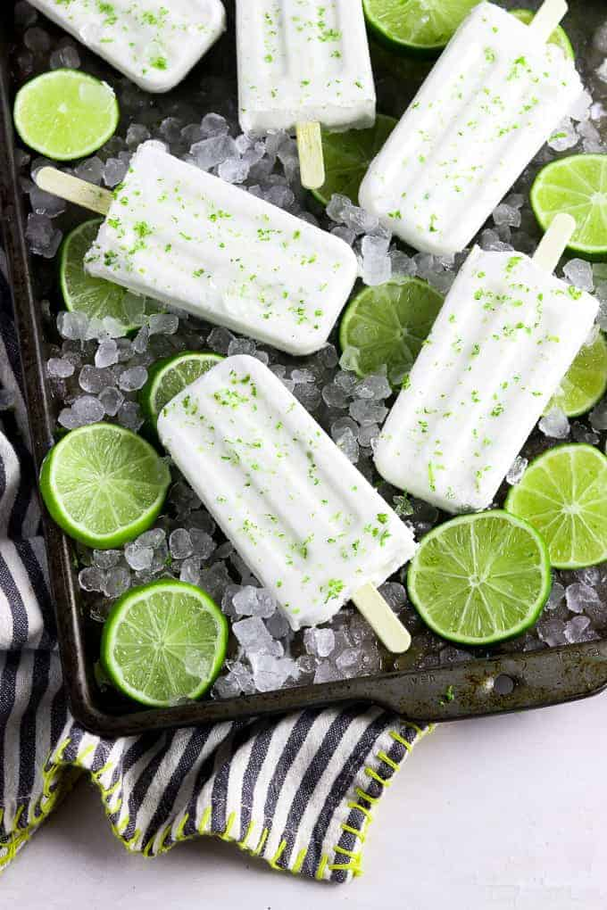 6 coconut lime popsicles on a baking tray on top of ice and limes.