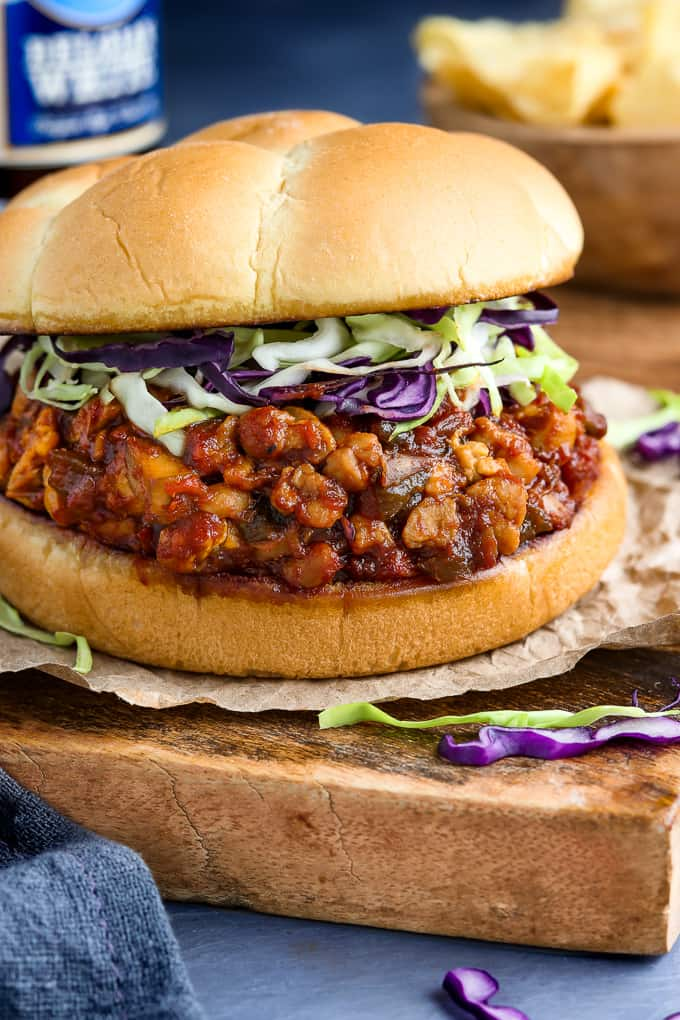 Side view of assembled vegan sloppy joes with chips and beverage in the background.