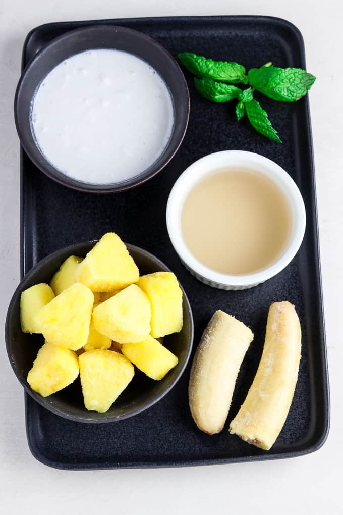 Pineapple, banana, coconut milk, fresh mint and coconut water on a black serving tray.