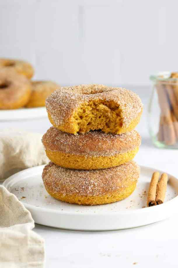 Three vegan pumpkin donuts on a white plate with cinnamon sticks and donuts in the background.
