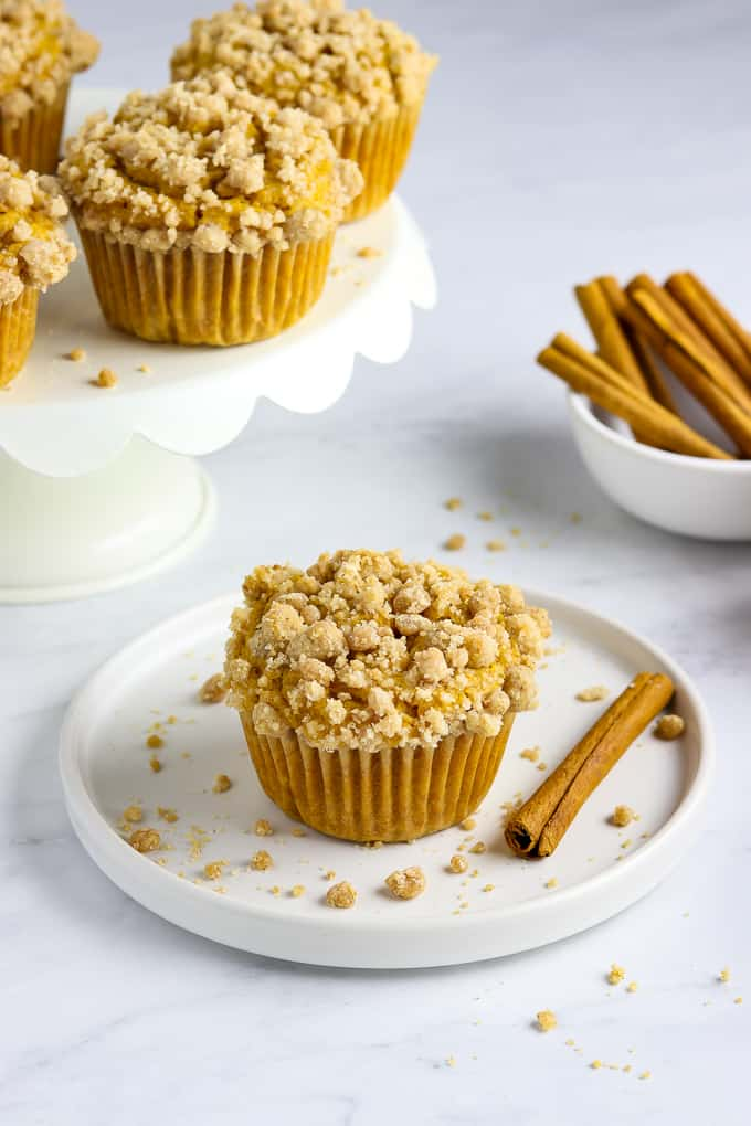 vegan pumpkin muffin on a white plate with muffins on a cake stand in the background.