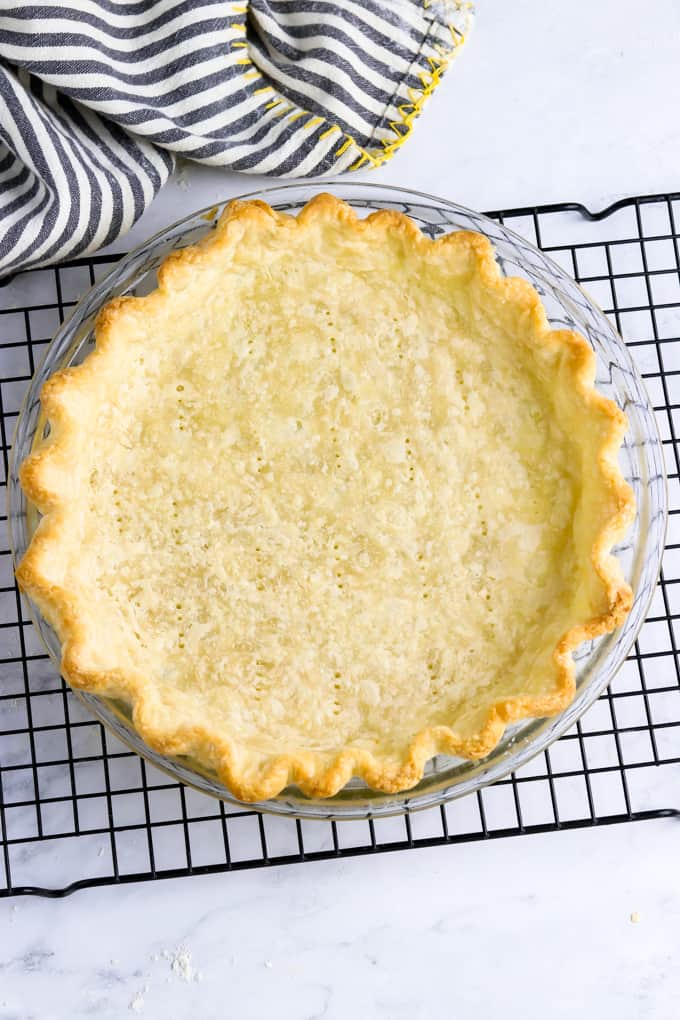 Fully baked vegan pie crust on a cooling rack.